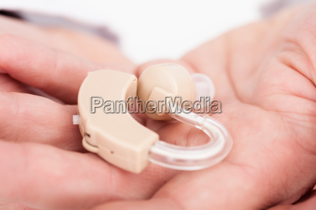 person holding hearing aid