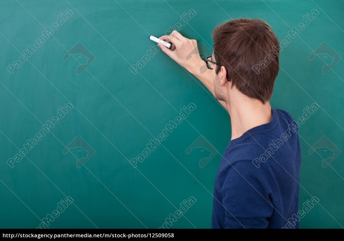 male, student, writing, on, chalkboard - 12509058