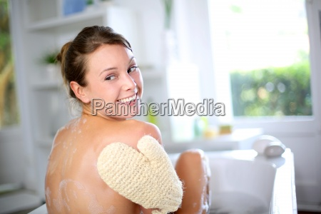 gorgeous woman scrubbing her back in