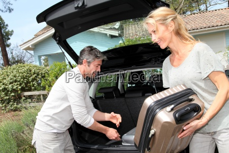 couple, putting, suitcases, in, car, trunk - 12512204