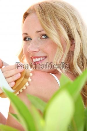 beautiful blond woman using massage brush