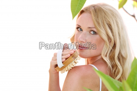beautiful blond woman using massage brush