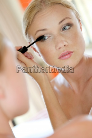 portrait, of, young, woman, putting, mascara - 12518632
