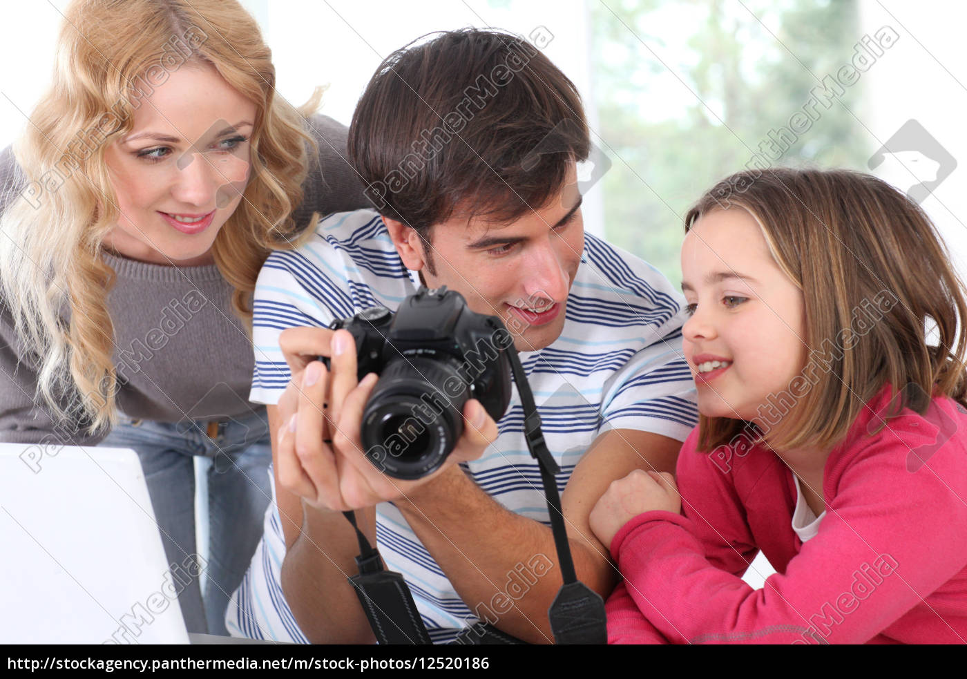 family, looking, at, pictures, on, camera - 12520186