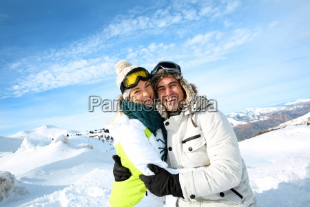 cheerful couple standong on mountain peak