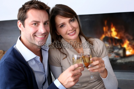 cheerful, couple, drinking, champaign, by, fireplace - 12521406