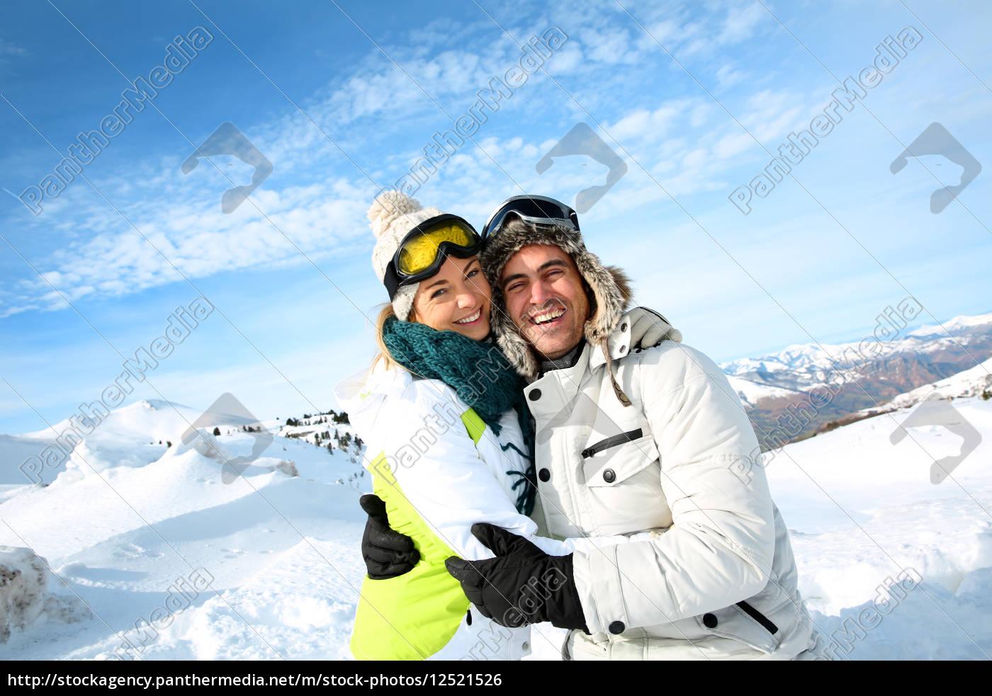 cheerful, couple, standong, on, mountain, peak - 12521526