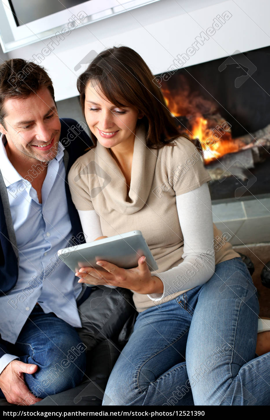 couple, sitting, by, fireplace, and, websurfing - 12521390