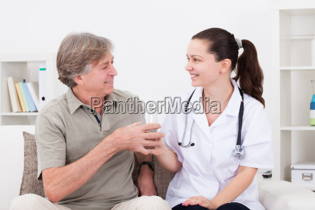 doctor offering glass of water to