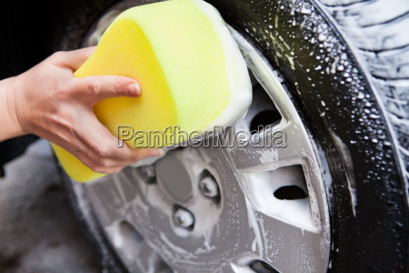 hand, washing, a, tire, with, sponge - 12525860