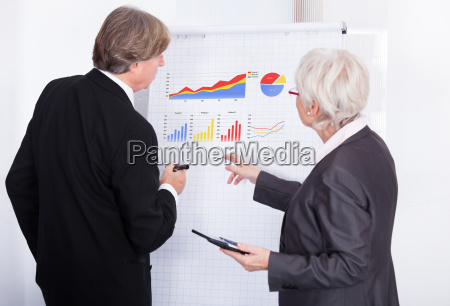 two businesspeople with calculator and flipchart