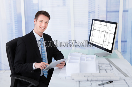 architect using digital tablet at computer