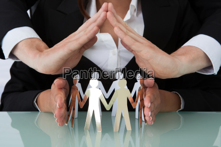 business people sheltering team of paper