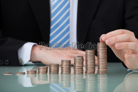 businessman, with, coins, stacked, as, bar - 12526678
