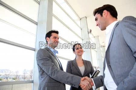 business partners shaking hands in meeting