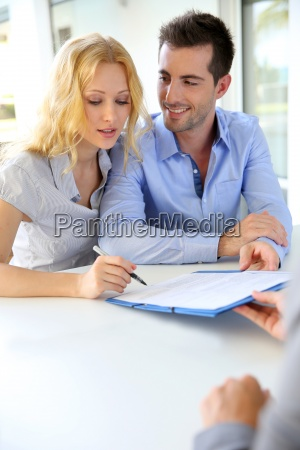 cheerful couple signing property contract with