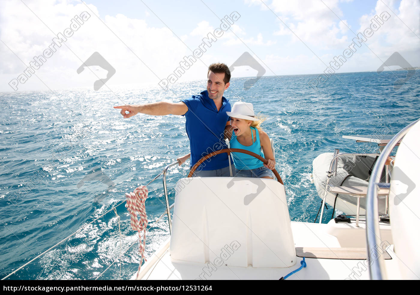 young, couple, navigating, on, a, yacht - 12531264