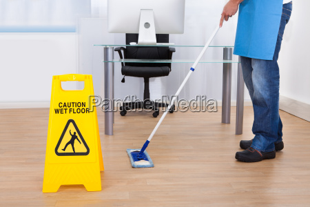 warning notice as a janitor mops