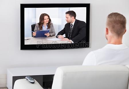 man sitting watching television at home