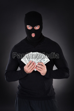 criminal in a balaclava holding a