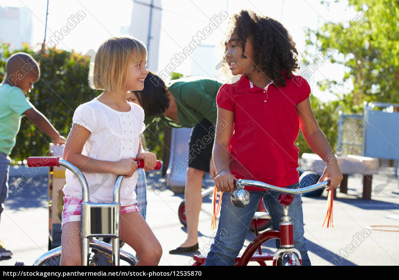 two, girls, riding, tricycles, in, playground - 12535870