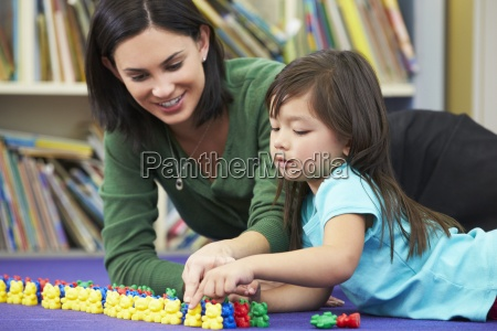 elementary pupil counting with teacher in