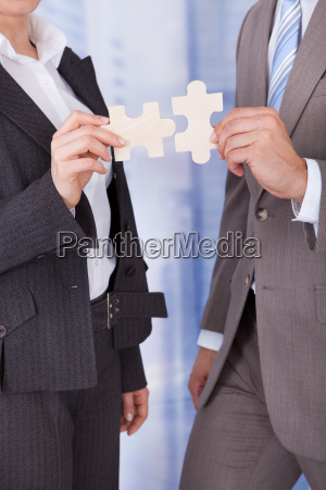 business people joining jigsaw pieces in
