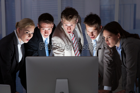 surprised business people looking at computer