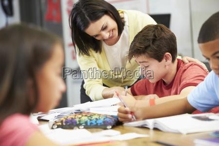 teacher helping pupils studying at desks