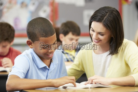 teacher reading with male pupil in