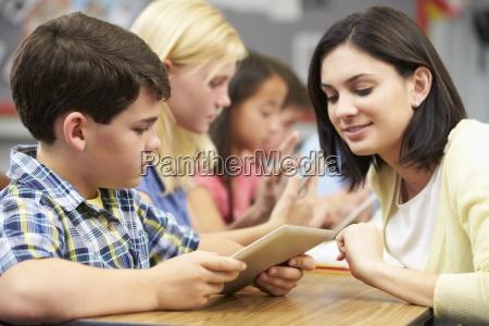 pupils, in, class, using, digital, tablet - 12536510