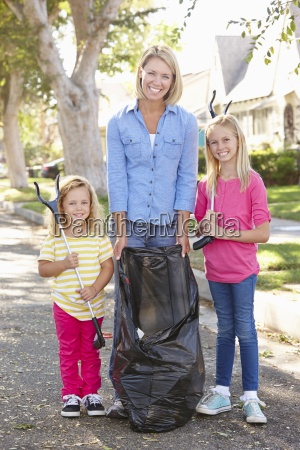 mother and daughters picking up litter