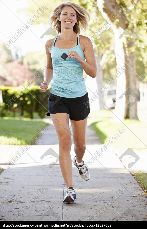 female, runner, exercising, on, suburban, street - 12537052