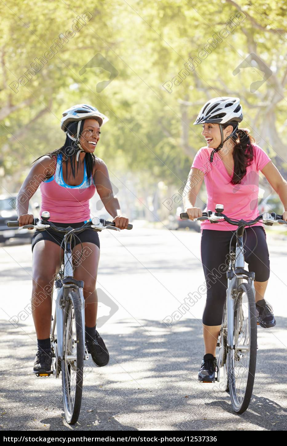 two, women, cycling, on, suburban, street - 12537336