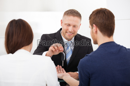 agent giving car key to couple