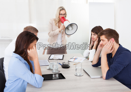 businesswoman shouting through megaphone on colleagues