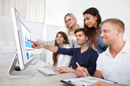 smiling businesspeople using desktop pc
