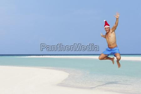 man, jumping, on, beach, wearing, santa - 12538522