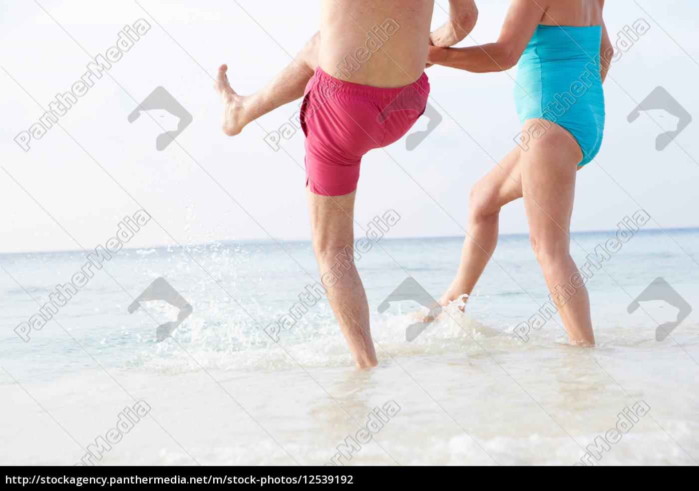 detail, of, senior, couple, splashing, in - 12539192