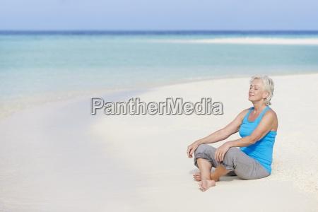 senior, woman, meditating, on, beautiful, beach - 12539084