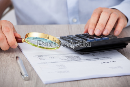 male auditor scrutinizing financial documents
