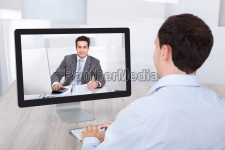 businessman video conferencing with coworker on