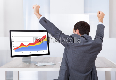 businessman celebrating success at computer desk