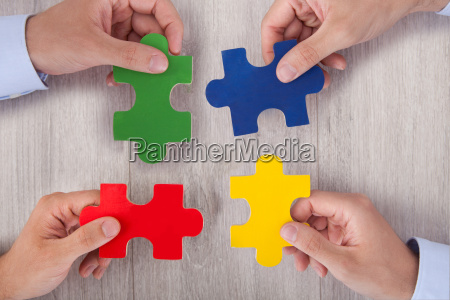 businesspeople joining multicolored puzzle pieces at