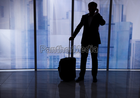 businessman with luggage using cell phone