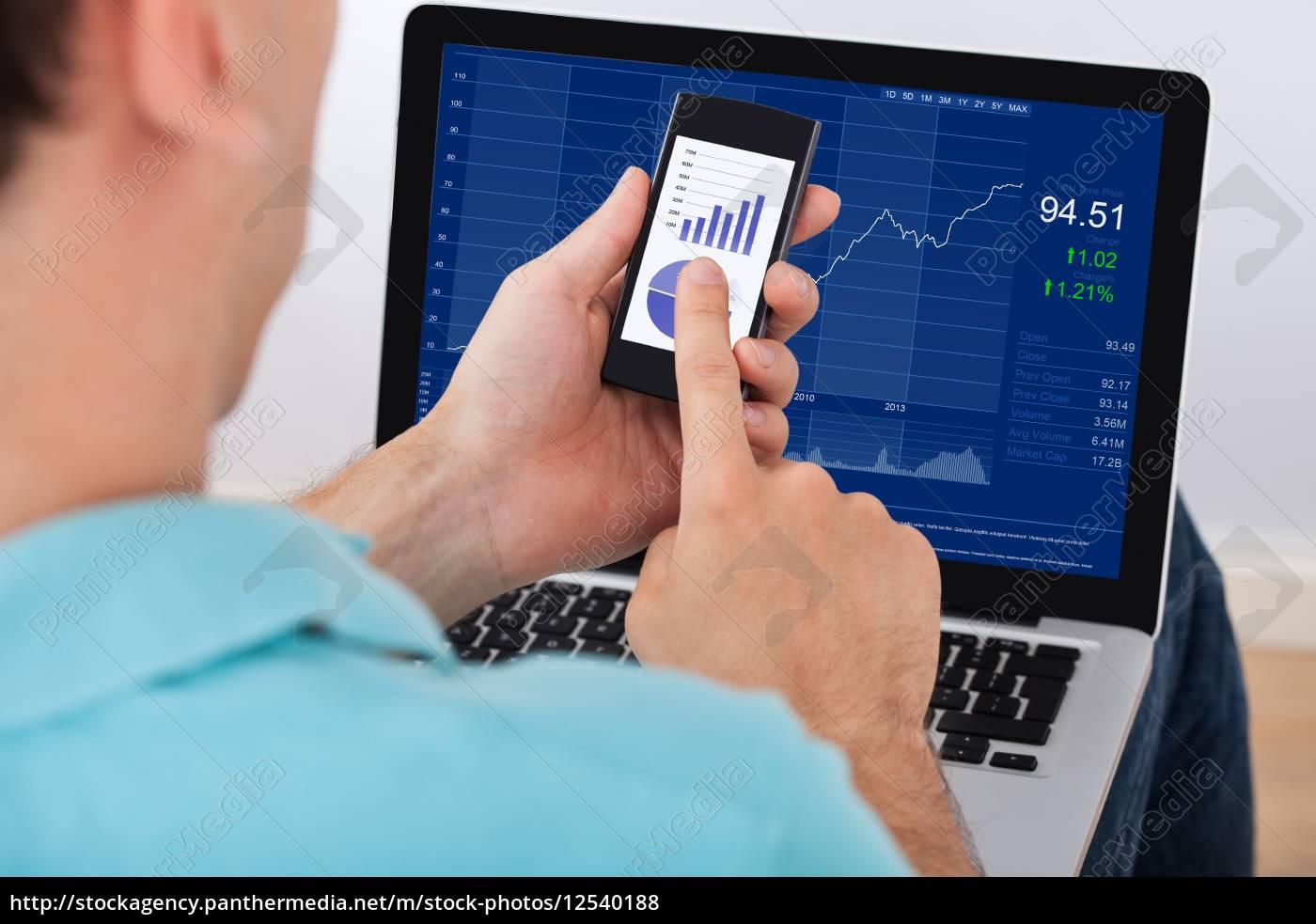 man, analyzing, stock, market, using, smartphone - 12540188