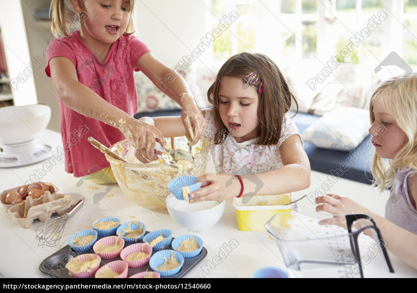 three, girls, making, cupcakes, in, kitchen - 12540660