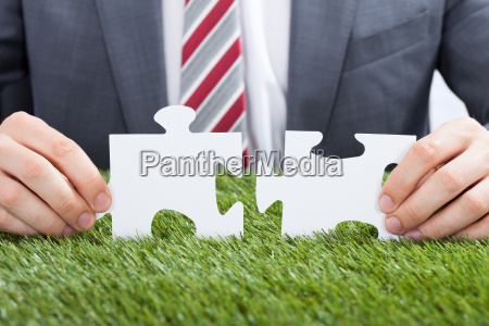 businessman joining puzzle pieces on grass
