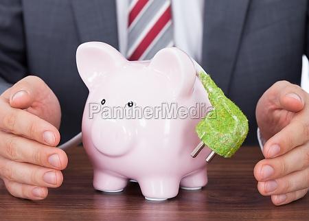 businessman shielding piggybank and green power