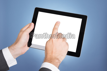 hand pointing at tablet computer screen